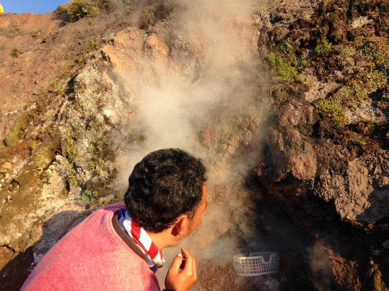 Adi boiling eggs in the steam of Mount Batur, Bali