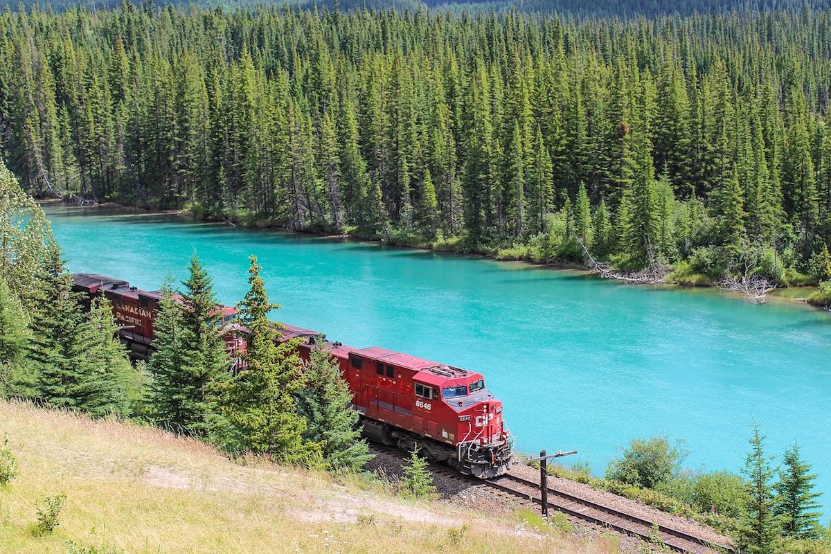Train passing a bright lake in Alberta in the summer