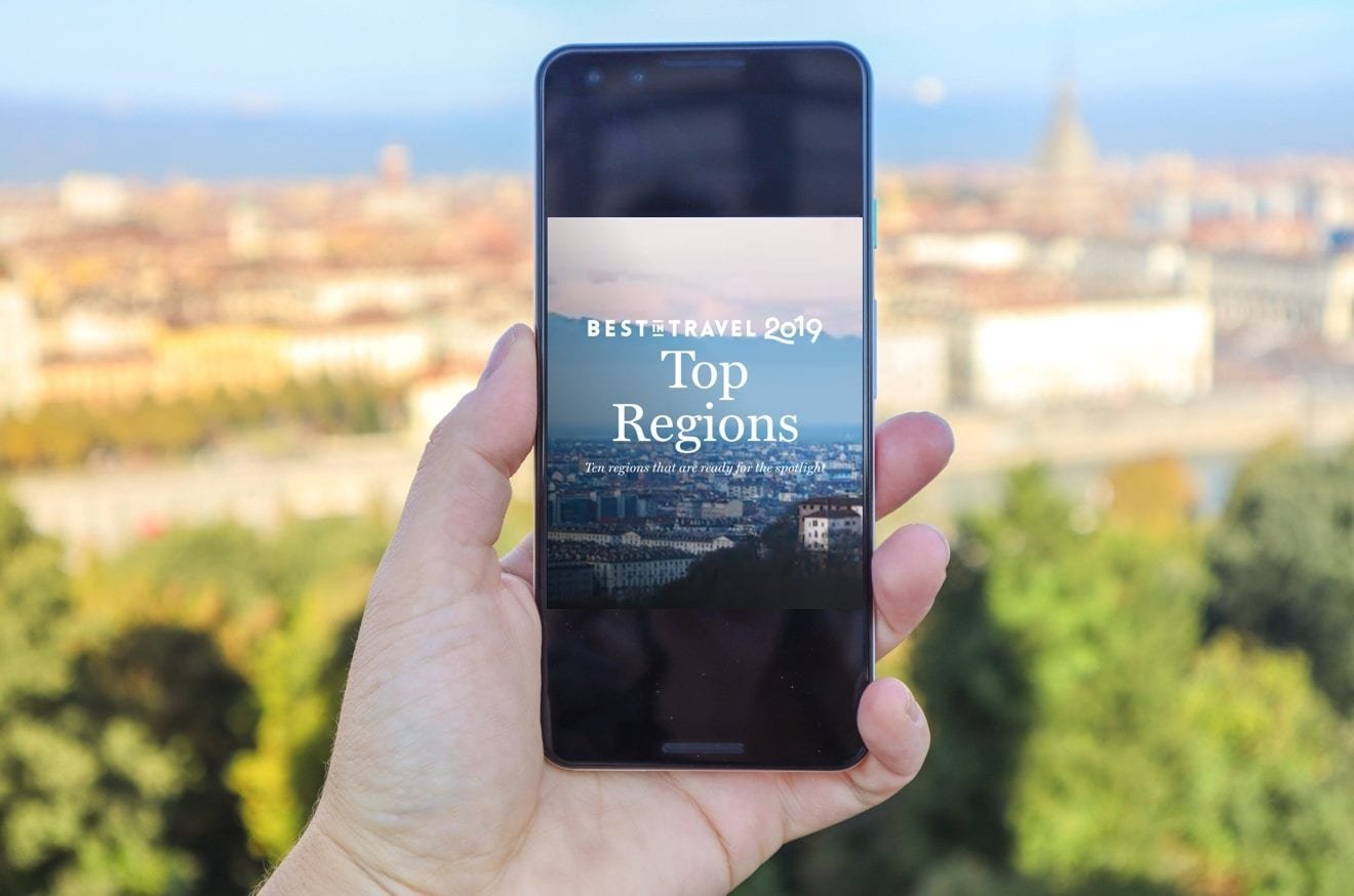 Best In Travel Region on phone with Turin backdrop